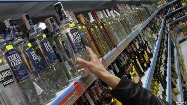 Serorang pembeli mengambil sebotol vodka dari jajaran minuman keras di sebuah supermarket di Benidorm, Rusia