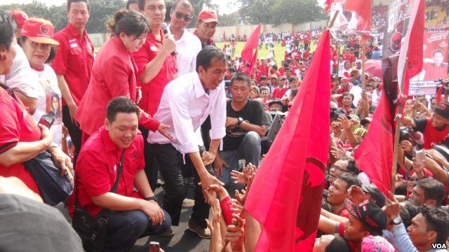 Calon Presiden dari PDI Perjuangan Jokowi bersalaman dengan para ribuan simpatisan dan kader PDI Perjuangan yang menghadiri kampanye terbuka Minggu 16 Maret 2014 di Gelanggang Olah Raga Cendrawasih Cengkareng Jakarta. (VOA/Andylala Waluyo