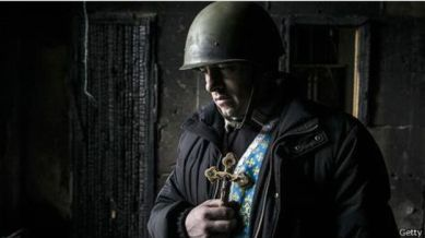 Pendeta di Ukraina memegang tanda salib di reruntuhan gedung Serikat Dagang di Kiev