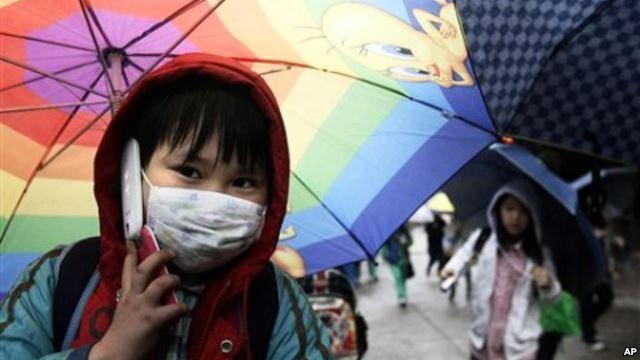 Seorang siswa SDI di Seoul, Korea Selatan, berbicara di ponselnya sambil memegang payung